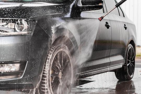 A man is washing a car at self service car wash. High pressure vehicle washer machine sprays foam.