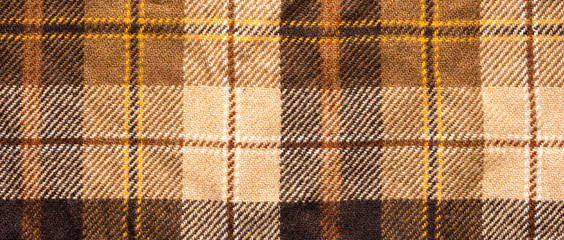 Brown checked fabric. Scottish wool. Fabric for coat plaid suit. Close-up. Background