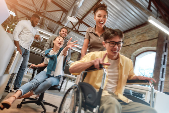Being disabled does not mean you can't be happy. Young positive asian man in wheelchair having fun with his colleagues at modern office