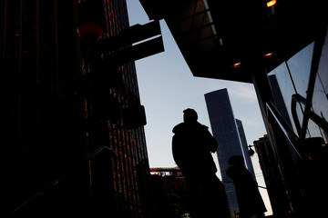 People are seen in silhouette walking during cold weather in the Manhattan borough of New York City, New York