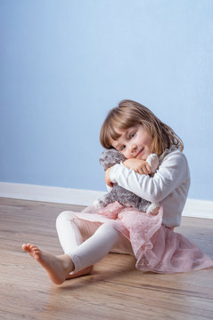 Girl hugs a fluffy cat toy staying on the floor.
