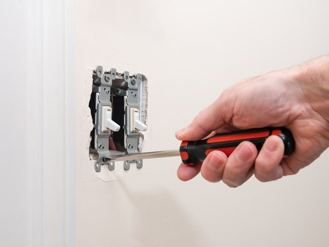 Male electrician repairing wall light switch panel. Handyman using screwdriver to install screw on light switch.