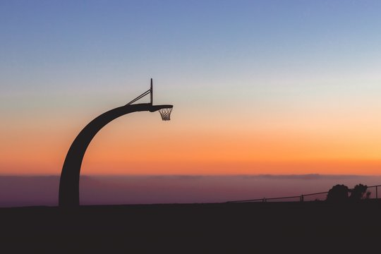 Silhouette of a basketball hoop with the beautiful view of sunset in the background