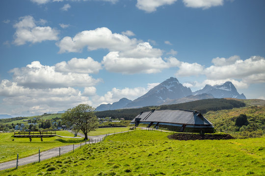 Lofotr long house, a home for vikings in the viking era, during daytime with white clouds. Mountains in the background. Architecture, history and viking concept.