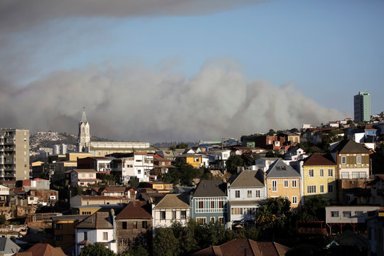 A cloud of smoke from a forest fire is seen above the neighbourhoods of Valparaiso