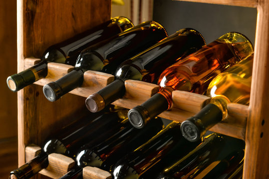 Wooden holder with bottles of wine in cellar