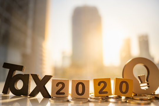Wood word TAX 2020 and stack of coins on blurred city scape with copy space using as background Income, tax, financial data concept.