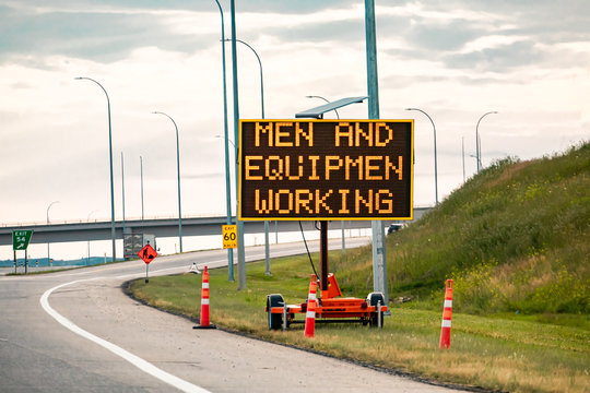 Temporary condition Variable message sign with orange barrels on the right roadside Men and equipment working, work zone on the Canadian highway roads