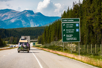 Zelfklevend Fotobehang Canada Information Road Green Sign, lake Louise, moraine lake, bow valley parkway, Vehicles on Canadian road between forest trees, mountains, Alberta, Canada