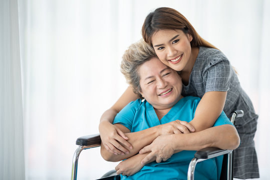 Asian daughter or care assistant helping support senior woman or mother