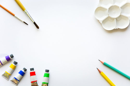 top view of brushes, color tubes, pencils and palette on white drawing pad background, copy space, flat lay, paintings art concept