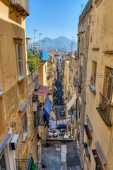 Narrow alleyway in the old town of Naples with Mount Vesuvius in the back