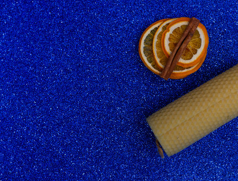Natural beeswax candle on a blue background Organic handicraft object Romantic candle made for the holiday Dried orange slices, cinnamon. Background made in trendy classic blue color of the year 2020.
