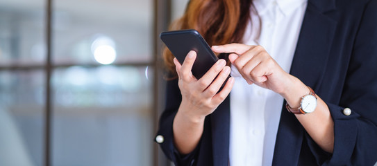 Closeup image of a businesswoman holding and using mobile phone