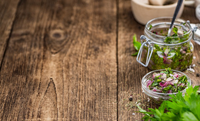 Wooden table with Chimichurri (detailed close-up shot; selective focus)