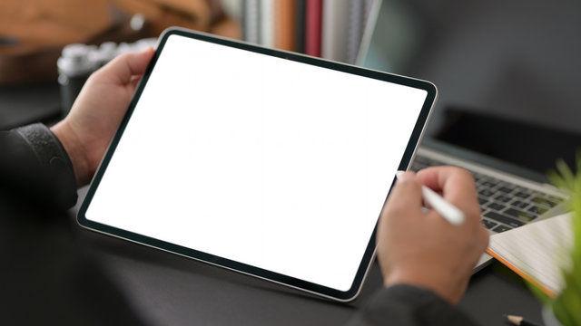 Cropped shot of young businessman using blank screen digital tablet in modern office