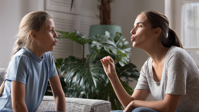 Young mom do pronunciation exercises with daughter