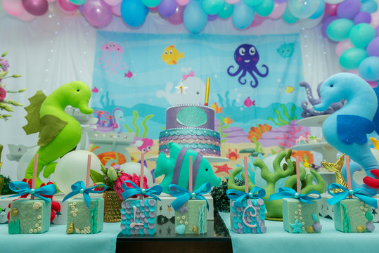Cake table overview decorated with the seabed theme. Children's party with octopus, seahorse, oysters, corals and colorful balloons. Party and fun concept.