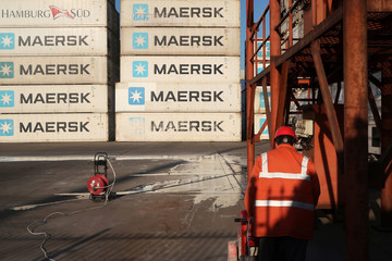 Worker is seen next to Maersk shipping containers at a logistics center nearTianjin por