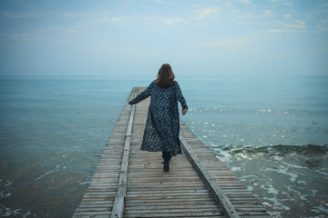 Young Girl Walking on the Pier to the Sea