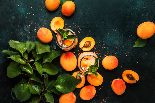 Healthy apricot smoothies in glass bottles and fresh fruits, top view