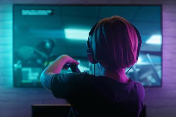 Fototapeta Little boy playing video game in the dark room obraz
