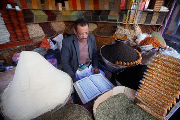 A spices vendor reads the Quran in his shop at a market place in the old quarter of Sanaa