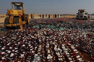 Steamrollers crush liquor bottles, during a ceremony to destroy confiscated contraband and goods unfit for human consumption on the outskirts of Karachi