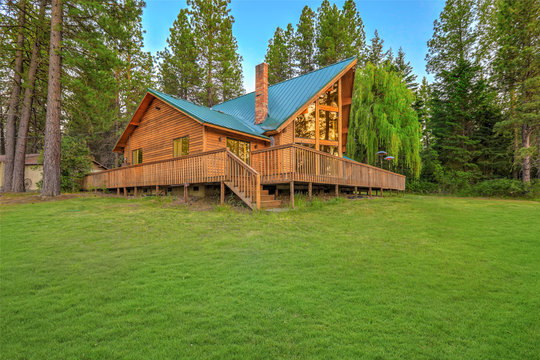 Luxury summer mountain cabin home with large green lawn and pine trees.
