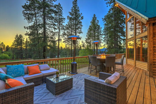 Luxury summer evening mountain home eteriors with cozy porch fire table and new furniture design.