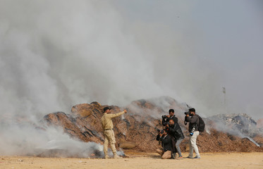Officer from Pakistani Customs poses for photographers as he takes a selfie near a burning pile of betel nuts on the outskirts of Karachi