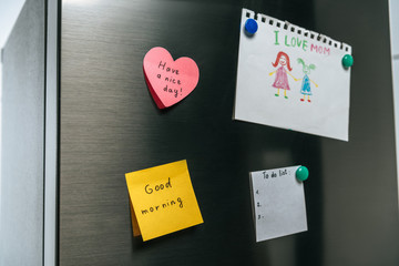 drawing of family and notes with wishes hanging on fridge