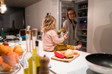Little girl sitting in the kitchen with her mother giving her a banana