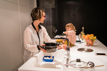 Mother preparing dinner in the kitchen with a little girl sitting next to her, showing her an egg