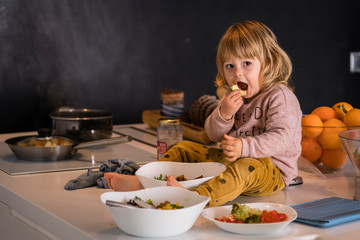 Little girl sitting on top of the kitchen surrounded by vegetable dishes and eating a piece of apple