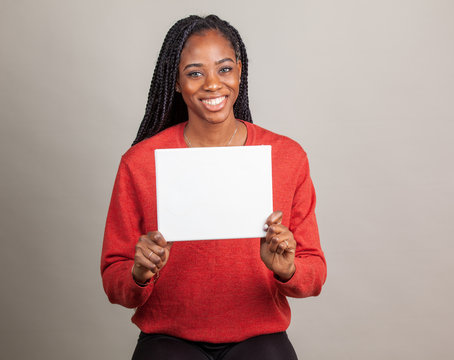 African American woman with blue eyes holding a sign with room for copy.