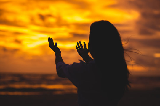 The shadow of a woman raised her hand to pray to God in heaven Style Silhouette