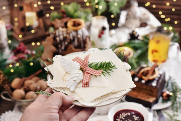 Christmas Eve wafer on white plate held above the festive table