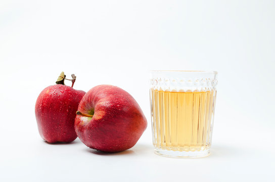Two red ripe apples and stylish glassware of apple juice on the white background