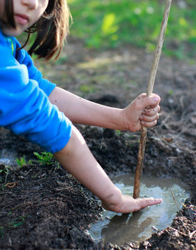 Grounded child playing with mud and stick for nature discovery
