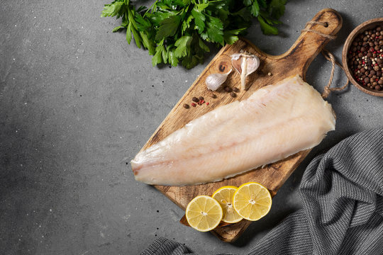Whitefish lightly salted on a wooden Board on a brown wooden table. Whole fillet of fish whitefish or muksun closeup. Top view with space for text