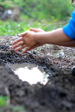 child playing with mud - blur hands for focus on pond
