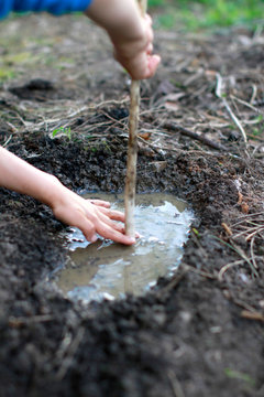 Anonymous child hands having fun playing with mud and water