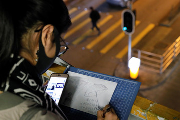 A woman writes a Christmas card for people who are in detention during the recent protests in Hong Kong