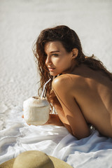Woman with Coconut Drink on the Beach
