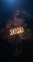 2020 vertical greeting text with particles and sparks on black night sky with colored fireworks on background, beautiful typography magic design, portrait orientation.