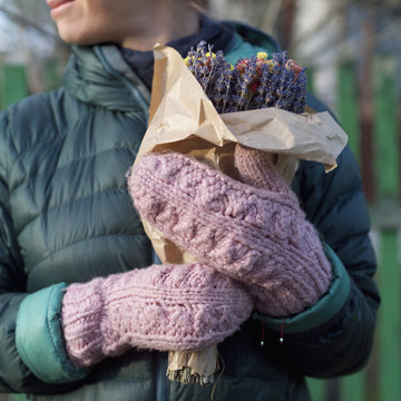 girl wearing wool gloves holding bouquet