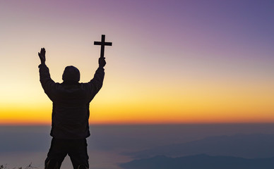 Human praying and holding christian cross for worshipping God at sunset sky background.Christian, Christianity, Religion copy space background.