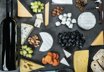 different varieties of cheese with fruits, nuts, dried fruits and kitchen utensils for cheese plate. Roquefort, Maasdam, emental, Gouda, Parmesan, mozzarella and other cheeses. The view from the top