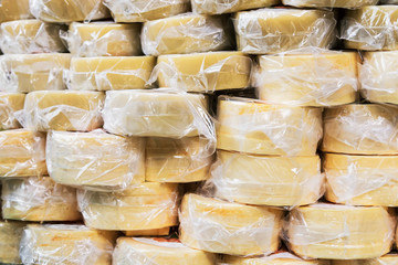many packages of cheese are on the counter of the store. background of cheese
